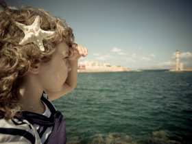 Sailor kid looking through the binoculars against blue sky background