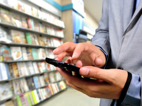 Young Business Man using Mobile Phone in Book store as E-education concept