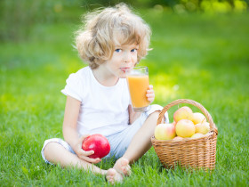 Happy child drinking apple juice in spring park