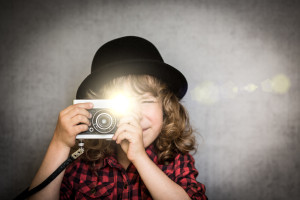 Hipster kid taking a photo using vintage film camera