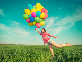 Happy girl playing with colorful toy balloons outdoors. Young woman having fun in green spring field against blue sky background. Freedom concept