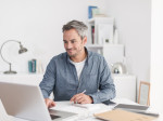 Portrait of a smiling grey hair man with beard, working at home