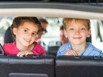 Rear view of a four people family in their car leaving for the weekend. Focus on the smiling little girl and blond boy who are completely turned on their black seat, looking at camera