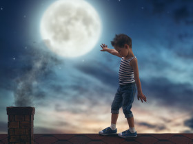 Child boy walks on the roof in the moonlight.